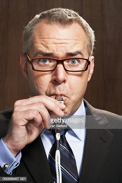 business man blowing whistle - whistle stock pictures, royalty-free photos & images