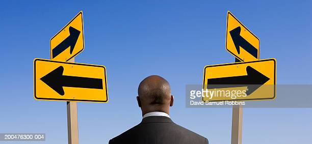 Business man by arrow signs (digital composite), rear view