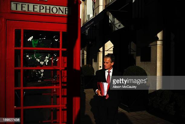Business man, carrying a file of papers, walks past a traditional English telephone box. His red tie matches the telephone box. The late afternoon...
