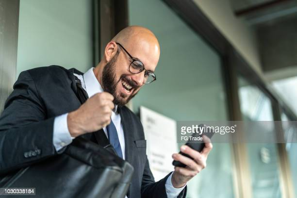 business man celebrating good news on mobile - lottery stock pictures, royalty-free photos & images