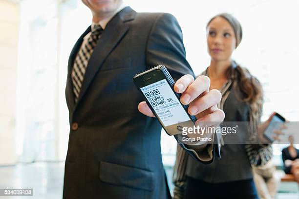 Business man checking in at airport security gate with smart phone