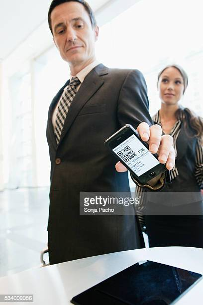 Business man checking in at security gate with smart phone