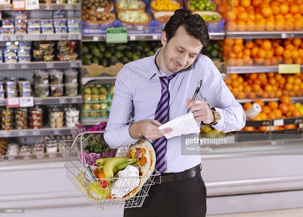 Business man checking shopping list : Bildbanksbilder