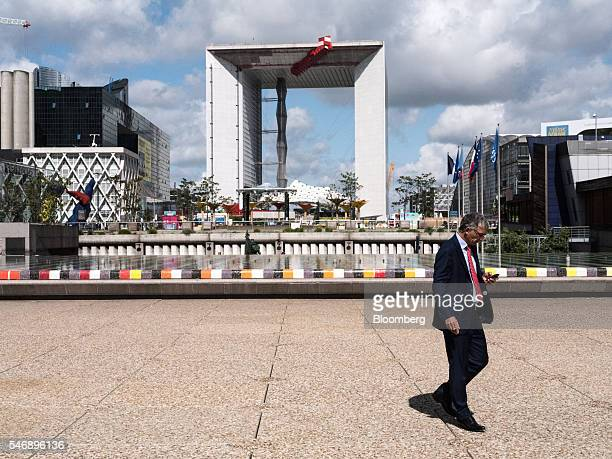 A business man checks his mobile device as the Grande Arche stands beyond in the La Defense business district in Paris France on Tuesday July 12 2016...