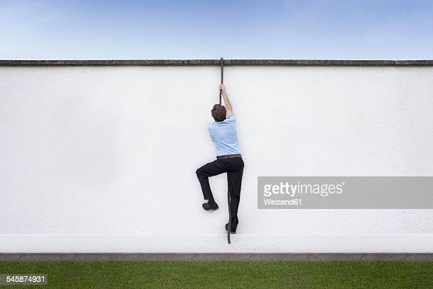 Business man climbing on wall