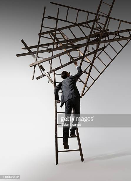 business man climbing up to cluster of ladders