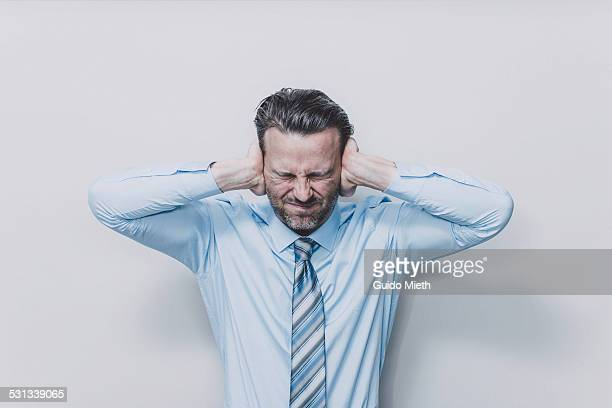 business man covering his ears. - mid volwassen mannen stockfoto's en -beelden