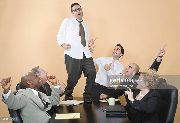 Business man dancing on table during business meeting
