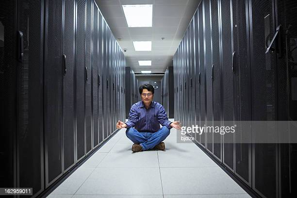 A business man doing yoga in the network server room