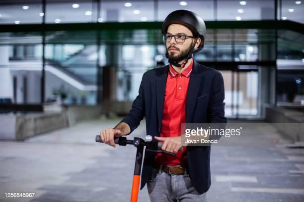 homme d'affaires conduisant son scooter électrique de poussée - casque de protection au sport photos et images de collection