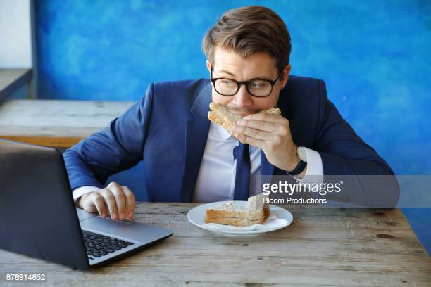 Business man eating a sandwich/lunch and using a laptop
