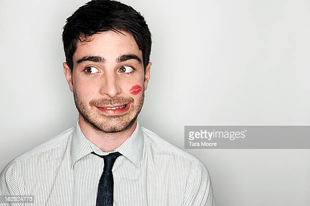 business man embarrassed with lipstick on face - verlegen stockfoto's en -beelden