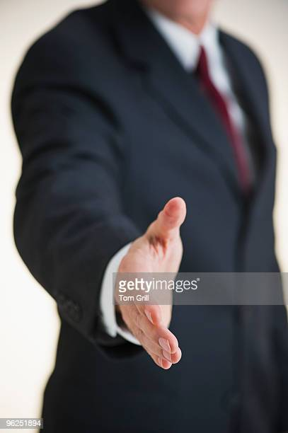 Business man extending a hand to shake