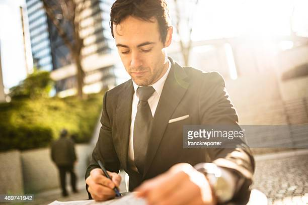 Business man filling papers on the city