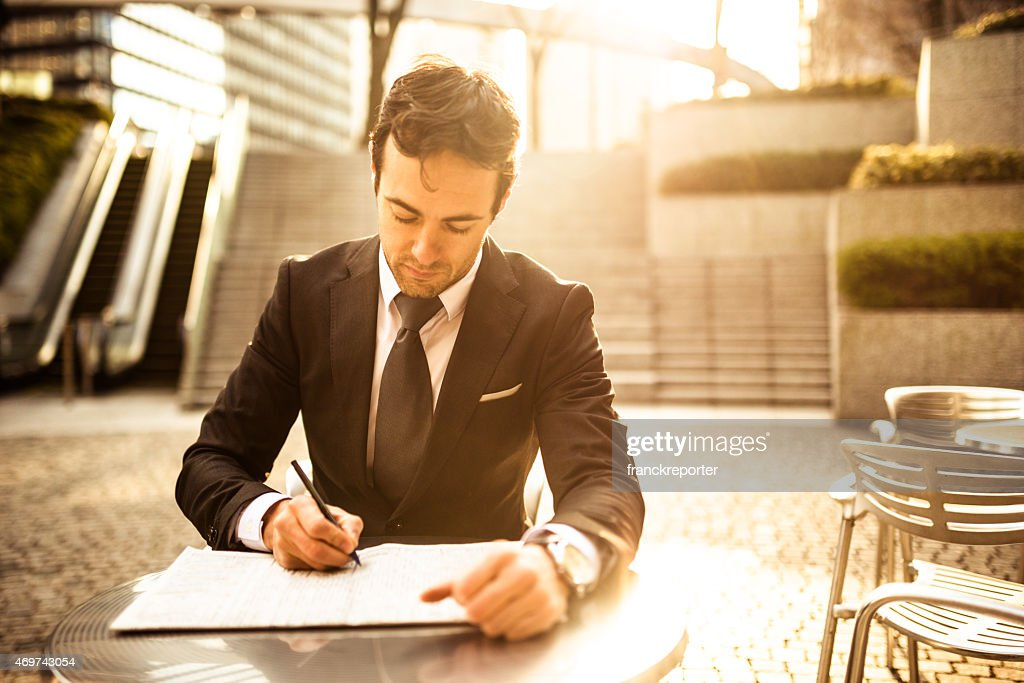 Business man filling papers on the city : Stock Photo