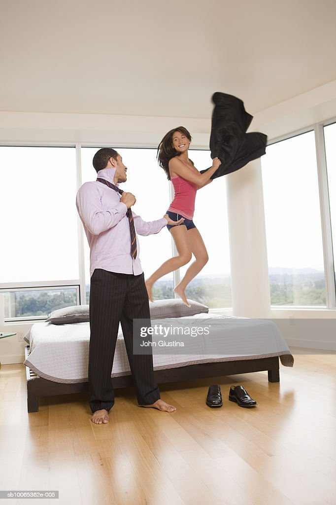 Business man getting dressed, woman jumping on bed waving suit jacket : Foto stock