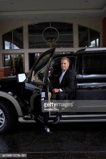 Business man getting out of car outside hotel, portrait