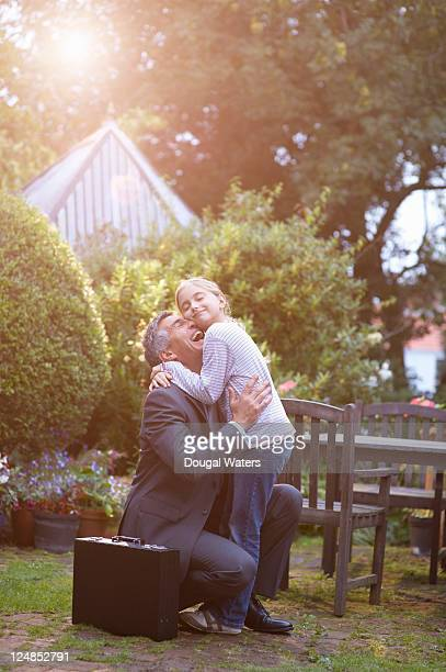 Business man greeting daughter in family garden.