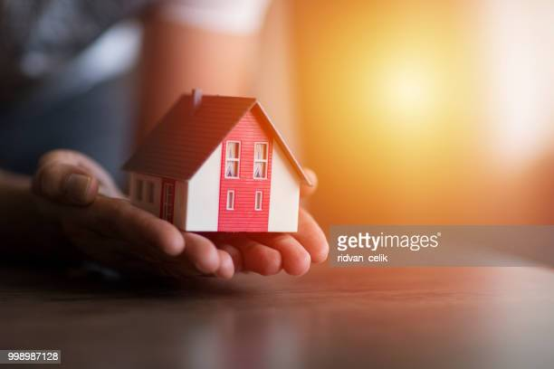 business man hand hold the house model saving small house - real estate stock pictures, royalty-free photos & images