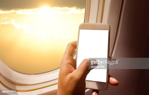 business man hand holding blank screen smart-phone on board of airplane near window seat and wing