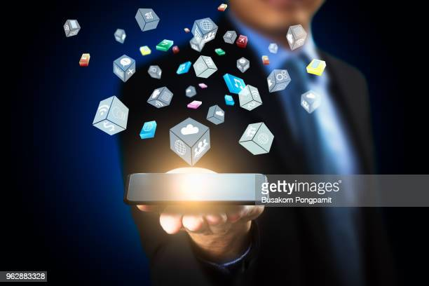Business man hand holding smartphone on blurred background using flying icons network and technology connection interface concept
