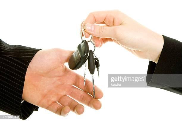 Bussinesman übergeben die Schlüssel, isoliert auf weiss