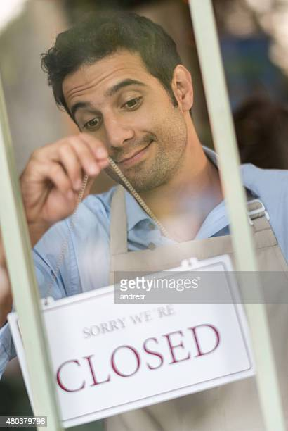 Business man hanging a closed sign on the door