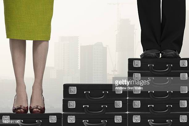 business man higher up stairs than business woman - prejudice stock photos and pictures