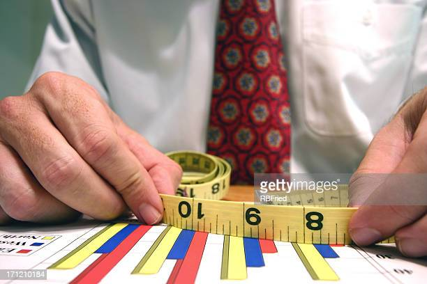 Business man holding a measurement tape over column charts