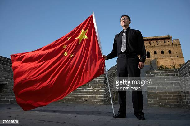 Business man holding a national flag on the Great Wall.