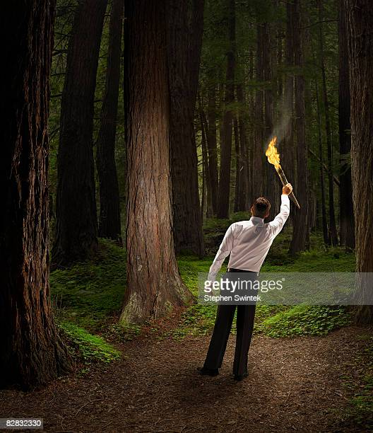 Business man holding a torch in a dark forest