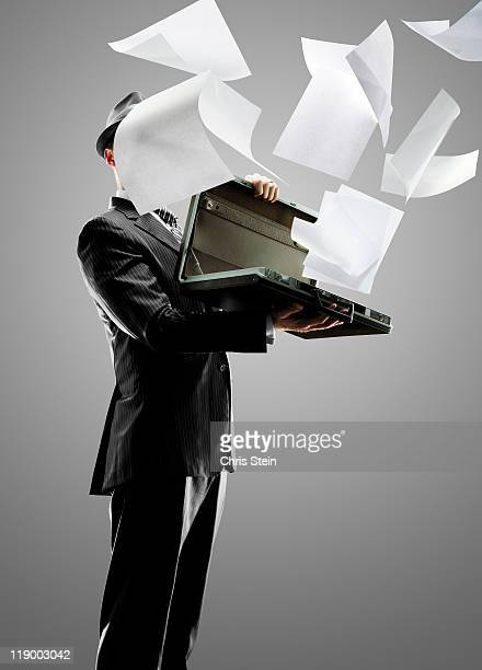 Business man holding and losing paper documents