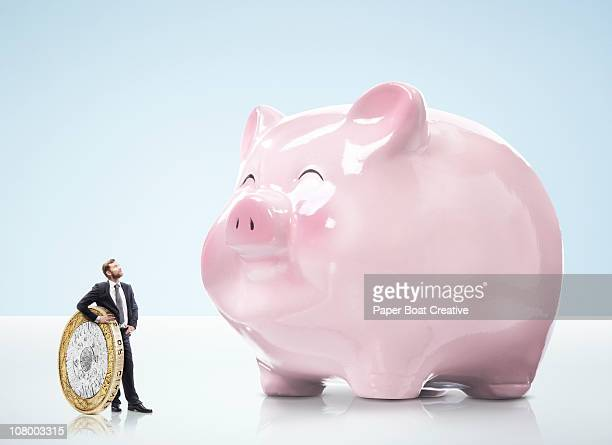 Business man holding coin, looking at piggy bank