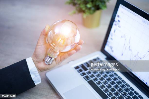 Business man holding light bulbs, ideas of new ideas with innovative technology and creativity.