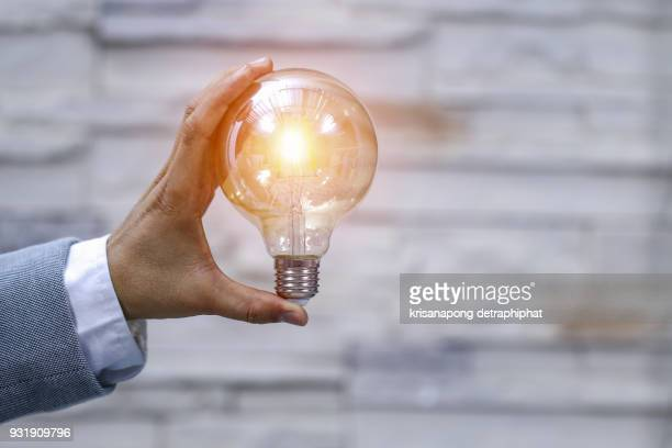 Business man holding light bulbs, ideas of new ideas with innovative technology and creativity