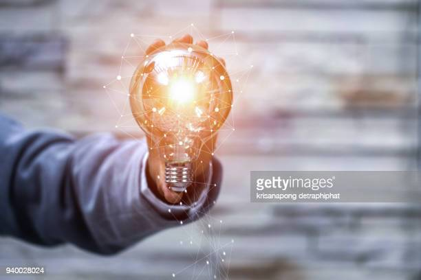 business man holding light bulbs, ideas of new ideas with innovative technology and creativity - lâmpada elétrica - fotografias e filmes do acervo