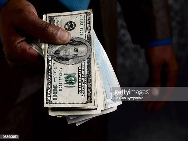 Business man holding out dollar bills