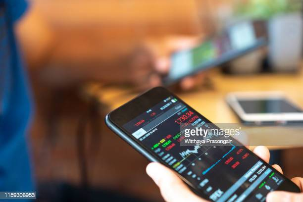 business man holding phone - stock trader stock pictures, royalty-free photos & images