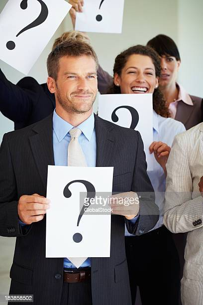 Business man holding question mark sign