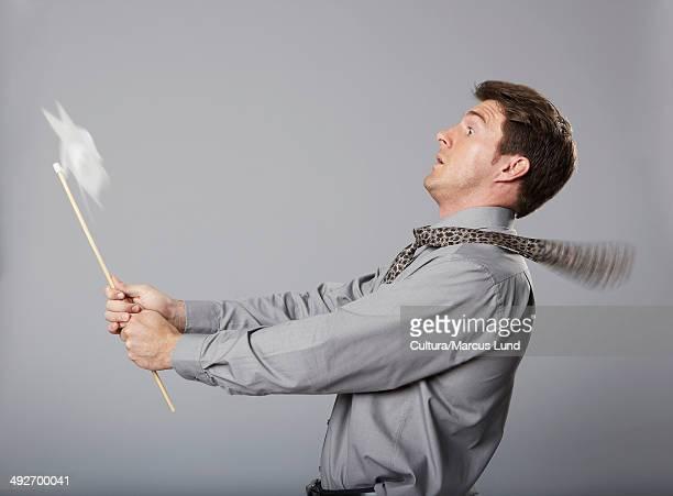 business man holding windmill - alleen één mid volwassen man stockfoto's en -beelden
