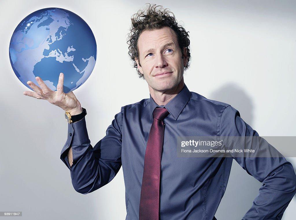 Business man holds up globe : Stock Photo