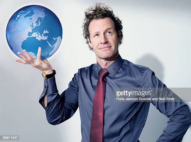 Business man holds up globe