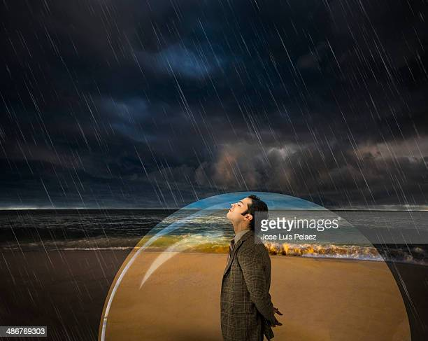 business man in a bubble while raining - people inside bubbles stock pictures, royalty-free photos & images