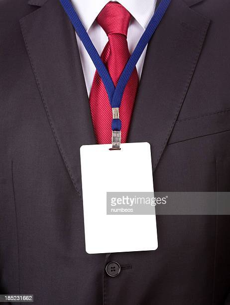 A business man in a suit and tie with a name tag lanyard