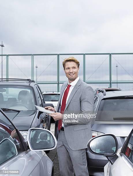 business man in car park, using digital tablet