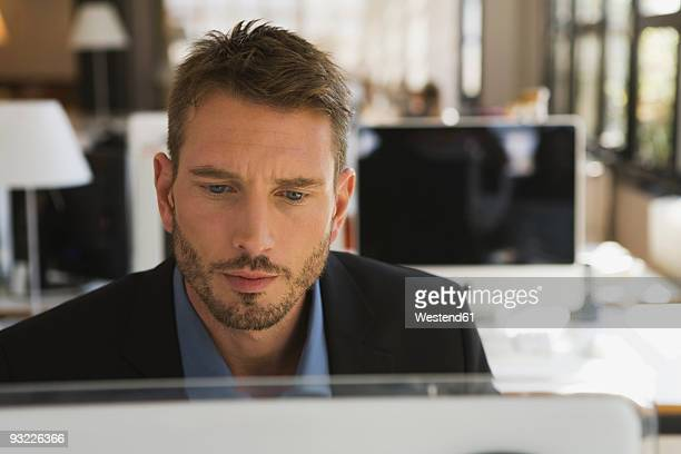 Business man in office using computer, portrait