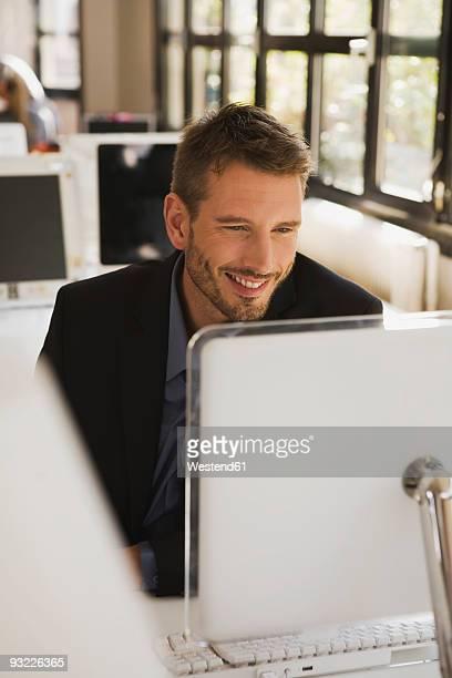 Business man in office using laptop, portrait