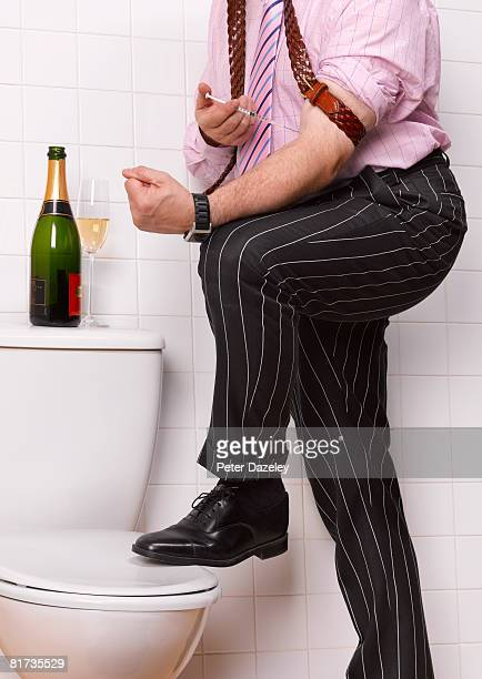 business man injecting heroin in bathroom. - heroin addict arm stock photos and pictures