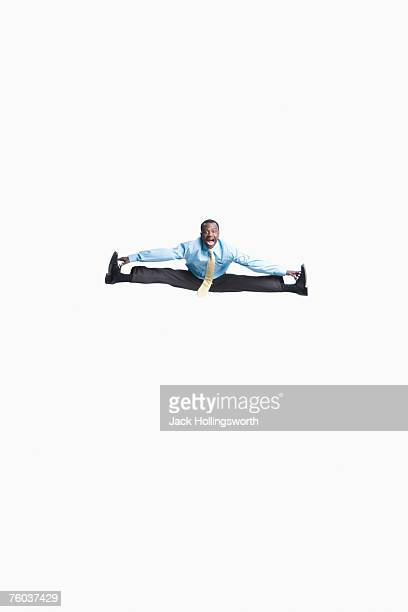 Business man jumping in air doing spilt, copy space