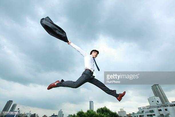 business man jumping in city
